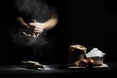 A mão do cozinheiro chefe trilha a farinha com o pino e os ingredientes de madeira do rolo Foto de Stock Royalty Free