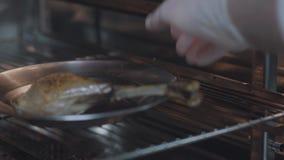 Mão do cozinheiro na luva branca da cozinha que põe a carne com o osso no fim do forno acima A preparação do cozinheiro chefe sab filme