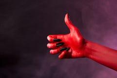 Mão do diabo vermelho que mostra os polegares acima imagem de stock royalty free
