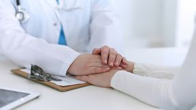 Mão do doutor da medicina que tranquiliza seu close up paciente fêmea Medicina, consolando e confiando o conceito nos cuidados mé imagem de stock