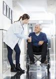 Mão do doutor Holding Senior Man na cadeira de rodas fotos de stock royalty free