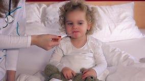 A mão do doutor do médico dá a colher com xarope líquido da medicina ao paciente da criança pequena filme