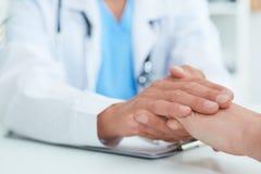 Mão do doutor masculino que tranquiliza seu close-up paciente fêmea Éticas médicas e conceito da confiança fotografia de stock