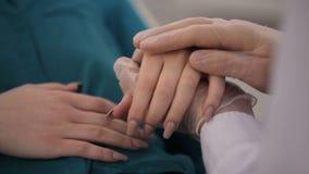 Mão do doutor que tranquiliza seu paciente fêmea filme