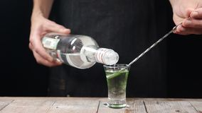 Mão do empregado de bar que derrama a bebida alcoólica forte em um tiro com uma colher fora de uma garrafa no movimento lento bár vídeos de arquivo