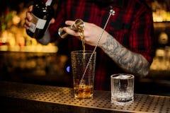 Mão do empregado de bar que derrama o álcool forte em um vidro de cocktail fotografia de stock