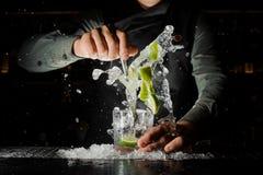 Mão do empregado de bar que espreme o suco fresco do cal que faz o cocktail de Caipirinha foto de stock
