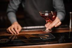 Mão do empregado de bar que guarda um vidro da bebida alcoólica decorada vermelha imagens de stock