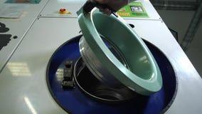 A mão do empregado que abre a máquina de lavar industrial video estoque