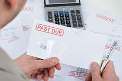 Mão do empresário com envelope passado-devido Imagens de Stock
