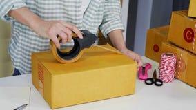 A mão do empresário em linha da mulher que usa a fita ao escritório de embalagem da caixa do pacote em casa, prepara o produto pa filme