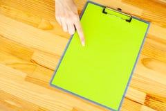 Mão do escritório que guarda um dobrador com um papel da cor verde no fundo da tabela de madeira Copyspace Lugar para o texto Imagens de Stock Royalty Free