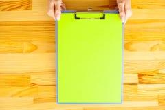 Mão do escritório que guarda um dobrador com um papel da cor verde no fundo da tabela de madeira Copyspace Lugar para o texto Imagem de Stock