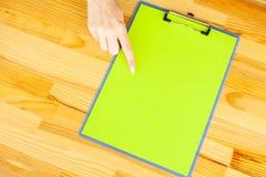 Mão do escritório que guarda um dobrador com um papel da cor verde no fundo da tabela de madeira Copyspace Lugar para o texto Foto de Stock