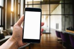 Mão do espaço de trabalho que guarda o dispositivo esperto do telefone fotos de stock