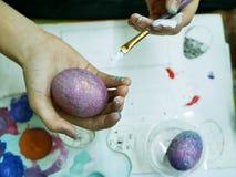 A mão do estudante guarda uma escova com pintura para ovos colorindo para a Páscoa imagens de stock royalty free