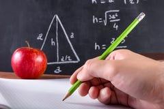 A mão do estudante masculino escreve no caderno com a pena de madeira verde Fotografia de Stock Royalty Free