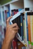 Mão do estudante que mantém a tabuleta digital na estante na biblioteca imagens de stock royalty free