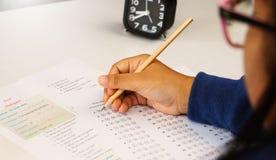 A mão do estudante que toma o teste inglês na classe fotos de stock