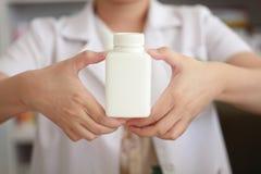 Mão do farmacêutico que guarda a garrafa da medicina Imagem de Stock Royalty Free