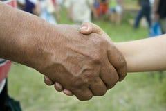 Mão do fazendeiro e do menino Fotografia de Stock
