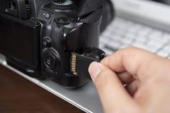 Mão do fotógrafo que guarda a câmera da inserção DSLR do cartão de memória do SD imagens de stock