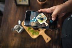 Mão do fundo da fotografia da mulher que usa o telefone celular para a tomada Imagens de Stock Royalty Free