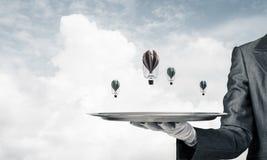 Mão do garçom que apresenta balões na bandeja Imagens de Stock