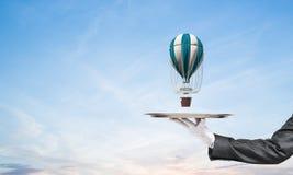 Mão do garçom que apresenta o balão na bandeja Foto de Stock