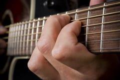 Mão do guitarrista que joga a guitarra acústica Imagem de Stock