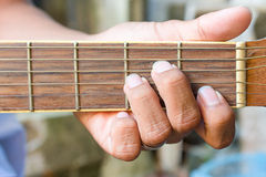 Mão do guitarrista que joga a guitarra acústica Fotografia de Stock