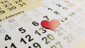 A mão do homem apresenta o coração de papel vermelho no mês do 14 de fevereiro em um calendário Feriado do amor para novo e velho vídeos de arquivo
