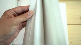 A mão do homem asiático abre o caderno na tabela de madeira filme