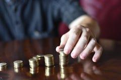 Mão do homem caucasiano que empilha moedas imagem de stock royalty free