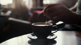 Mão do homem do close-up que agita o café com leite usando uma colher vídeos de arquivo