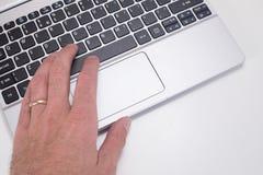 Mão do homem com aliança de casamento usando o teclado do portátil Fotografia de Stock