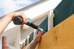 A mão do homem com chave de fenda prende o painel de madeira Imagens de Stock Royalty Free