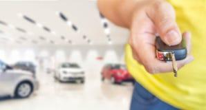 Mão do homem com chave do carro na sala de exposições do carro da foto do borrão fotos de stock royalty free