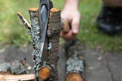 A mão do homem com costeletas de um machado um log Machado no log fotografia de stock