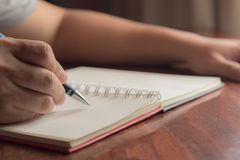 Mão do homem com escrita da pena no caderno Foto de Stock