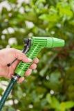 Mão do homem com o jardim molhando da mangueira Foto de Stock