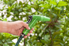 Mão do homem com o jardim molhando da mangueira Imagens de Stock