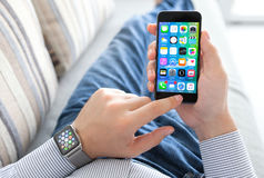 Mão do homem com o relógio de Apple que guarda o iPhone Fotos de Stock