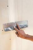 Mão do homem com a pá de pedreiro que emplastra uma placa de gesso Foto de Stock Royalty Free