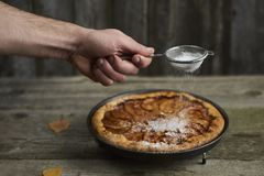 a mão do homem com a peneira que polvilha o pó do açúcar sobre o appl caseiro Imagem de Stock
