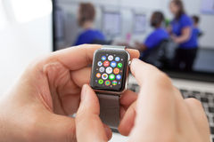Mão do homem com relógio de Apple e ícone do app na tela Fotos de Stock Royalty Free