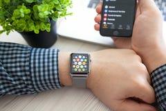 Mão do homem com relógio de Apple e ícone do app na tela Fotos de Stock
