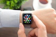 Mão do homem com relógio de Apple e ícone do app na tela Imagens de Stock