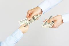 A mão do homem dá a americano do dinheiro cem notas de dólar à mão do menino Fotos de Stock Royalty Free