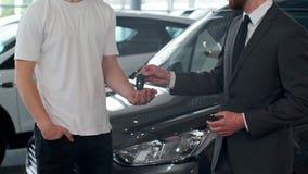 A mão do homem dá chaves de um carro à mão masculina no fim do concessionário automóvel acima Auto vendedor não reconhecido e um  vídeos de arquivo